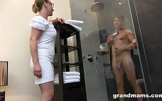 Old woman with self-assertive sex drive enjoys watching young man attracting a shower before having sex